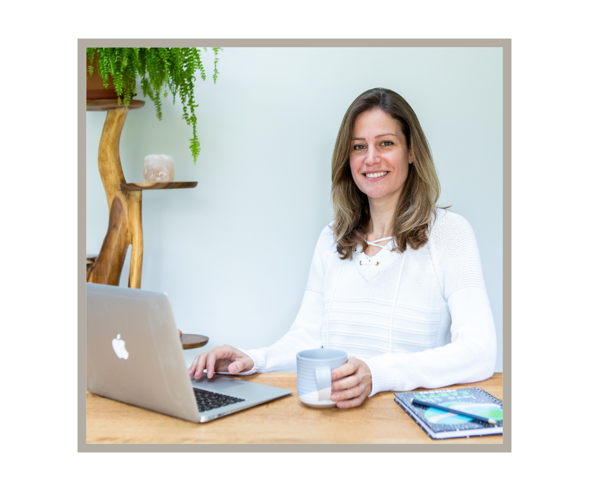 The founder of Plastic-Free Things sitting at a table smiling with laptop, cup of tea, note pad and a plant.