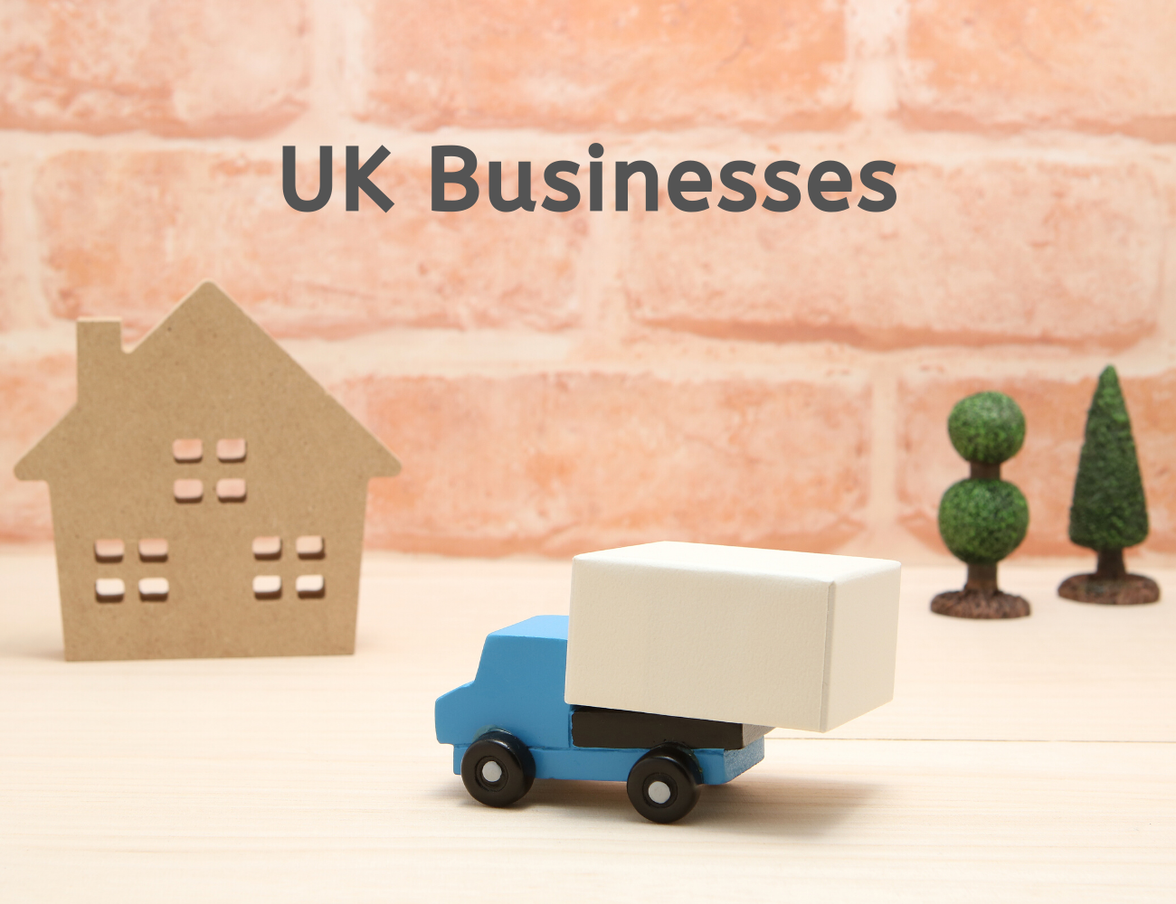 """Model car delivering a parcel to a model house with trees and the words """"UK businesses""""."""